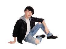 Hombre asiático joven que se sienta en piso Imagen de archivo libre de regalías
