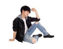 Hombre asiático joven que se sienta en piso Imagenes de archivo