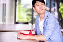 Hombre asiático joven que se sienta pacientemente en restaurante del café y que sostiene un actual regalo que da alguien especial imagenes de archivo