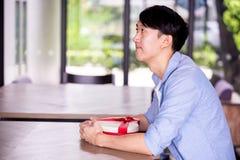 Hombre asiático joven que se sienta pacientemente en restaurante del café y que sostiene un actual regalo que da alguien especial fotos de archivo