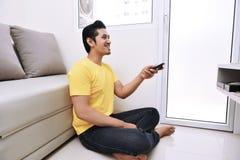 Hombre asiático joven que sostiene la TV de observación teledirigida mientras que se sienta foto de archivo