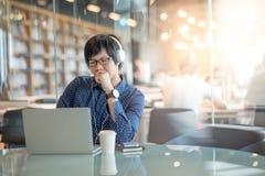 Hombre asiático joven que trabaja con el ordenador portátil en biblioteca Foto de archivo libre de regalías