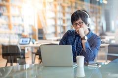 Hombre asiático joven que trabaja con el ordenador portátil en biblioteca Imagenes de archivo