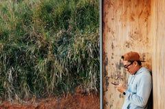 Hombre asiático joven que usa el soporte del teléfono móvil contra ingenio de madera de la pared Fotos de archivo libres de regalías