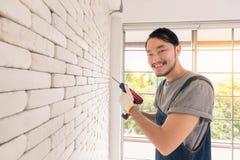 Hombre asiático joven que usa el taladro eléctrico en la pared de ladrillo blanca en sitio imagen de archivo
