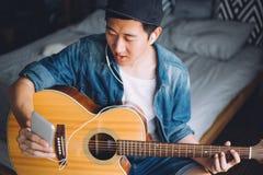 Hombre asiático joven que usa un teléfono móvil con los auriculares mientras que toca la guitarra en dormitorio acogedor Fotografía de archivo