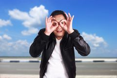 Hombre asiático joven que ve los fingeres binoculares del canal Fotografía de archivo
