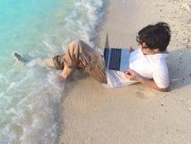 Hombre asiático joven relajado con el ordenador portátil que se acuesta en la arena de la playa tropical en día de vacaciones Imagenes de archivo
