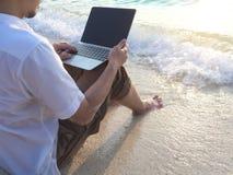 Hombre asiático joven relajado con el ordenador portátil que se sienta en la arena de la playa tropical Concepto de las vacacione Imágenes de archivo libres de regalías
