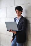 Hombre asiático ocasional elegante con la computadora portátil Fotografía de archivo