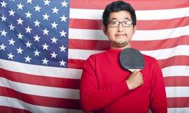 Hombre asiático orgulloso que sostiene la paleta de los tenis de mesa contra bandera de los E.E.U.U. Fotos de archivo
