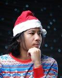 Hombre asiático pensativo que lleva Santa Hat y el suéter de la Navidad fotografía de archivo