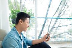Hombre asiático pensativo que usa smartphone en dormitorio en casa imagenes de archivo
