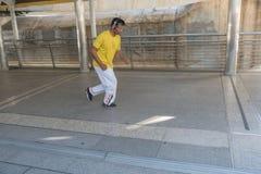 Hombre asiático que activa con música de los auriculares en la ciudad Imagenes de archivo