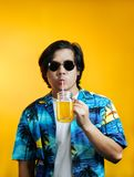 Hombre asiático que bebe a Juice Wearing Sunglasses anaranjado contra Yello fotos de archivo libres de regalías
