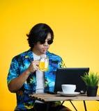 Hombre asiático que bebe a Juice While Working With Laptop anaranjado en suma imagenes de archivo