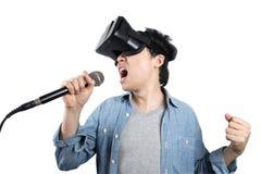 Hombre asiático que canta con VR Imagen de archivo