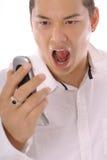 Hombre asiático que grita en el teléfono móvil Imágenes de archivo libres de regalías