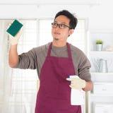 Hombre asiático que hace tareas de la casa Imágenes de archivo libres de regalías