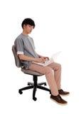 Hombre asiático que mecanografía en su ordenador portátil Imagen de archivo