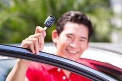 Hombre asiático que muestra llave de su coche Imagen de archivo libre de regalías