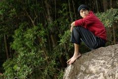 Hombre asiático que parece asentado en roca Imágenes de archivo libres de regalías