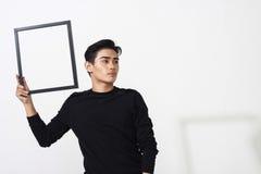 Hombre asiático que presenta con el marco vacío Fotografía de archivo libre de regalías