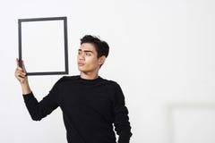 Hombre asiático que presenta con el marco vacío Fotos de archivo libres de regalías