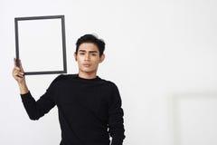 Hombre asiático que presenta con el marco vacío Foto de archivo libre de regalías