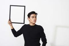 Hombre asiático que presenta con el marco vacío Imagenes de archivo