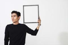 Hombre asiático que presenta con el marco vacío Fotos de archivo