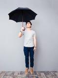 Hombre asiático que se coloca con el paraguas Imágenes de archivo libres de regalías