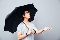 Hombre asiático que se coloca con el paraguas Imagen de archivo