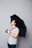 Hombre asiático que se coloca con el paraguas Imagen de archivo libre de regalías