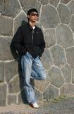 Hombre asiático que se inclina contra una pared Foto de archivo libre de regalías