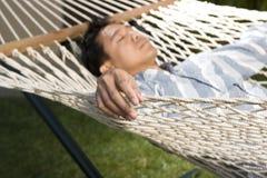 Hombre asiático que se relaja en una hamaca Fotos de archivo libres de regalías
