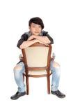 Hombre asiático que se sienta al revés en silla Imágenes de archivo libres de regalías