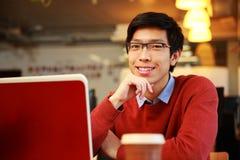 Hombre asiático que se sienta en la tabla con el ordenador portátil Foto de archivo