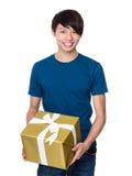 Hombre asiático que se sostiene con la actual caja grande de oro Fotografía de archivo