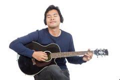 Hombre asiático que toca la guitarra con el auricular Foto de archivo