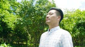 Hombre asiático que toma la respiración profunda, sonriendo y disfrutando de la naturaleza al aire libre en la cámara lenta almacen de metraje de vídeo