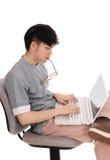 Hombre asiático que trabaja en su ordenador portátil Foto de archivo