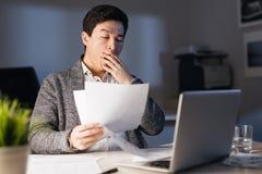 Hombre asiático soñoliento que trabaja en horas extras foto de archivo libre de regalías