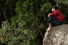 Hombre asiático solo que se sienta en roca Imagen de archivo libre de regalías