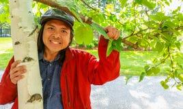 Hombre asiático sonriente que lleva a cabo la rama de un árbol de abedul Fotografía de archivo libre de regalías