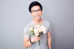 Hombre asiático sonriente que sostiene las flores Fotos de archivo