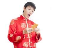 Hombre asiático Sostener el dinero en sobres rojos Año Nuevo chino en wh Imágenes de archivo libres de regalías