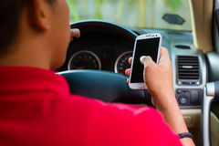 Hombre asiático texting mientras que conduce
