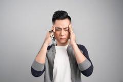 Hombre asiático thoughful triste joven que tiene dolor de cabeza después de trabajo imagen de archivo