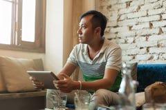 Hombre asiático triste que usa la tableta que se sienta en Imagenes de archivo